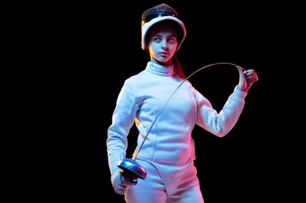 Ready. teen girl in fencing costume with sword in hand isolated on black wall, neon light. young model practicing and training in motion, action. copyspace. sport, youth, healthy lifestyle.
