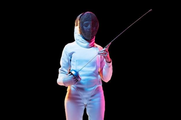 준비된. 검은 배경, 네온 빛에 고립 된 손에 칼으로 펜싱 의상에서 십 대 소녀. 젊은 모델 연습과 운동, 행동 훈련. copyspace. 스포츠, 젊음, 건강한 라이프 스타일.