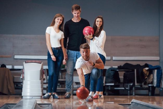 Pronto a lanciare. i giovani amici allegri si divertono al bowling durante i fine settimana
