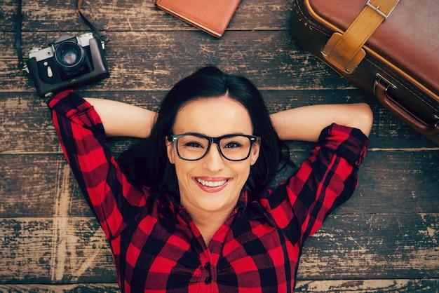 大きな旅行の準備ができました。堅木張りの床に横たわって、スーツケースとカメラを彼女の近くに置いて笑っているアイウェアの美しい若い女性の上面図