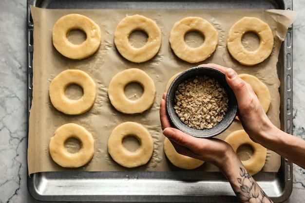 Готовое круглое печенье запечь на противне с пергаментной бумагой. миска измельченного арахиса в руках. горизонтальное фото, вид сверху.