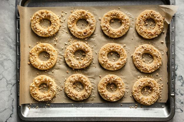 Готовое печенье круглое, посыпанное измельченным арахисом, на противне с пергаментной бумагой. горизонтальное фото, вид сверху.