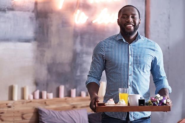 幸せになる準備ができました。朝食と結婚指輪のトレイを持って、笑顔でガールフレンドへの提案の準備をしている喜んでいる若いアフリカ人。