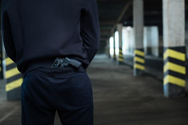 사용할 준비가되었습니다. 위험한 공격적인 잘 지어진 범죄자의 등 뒤에 보관되는 권총의 클로즈업