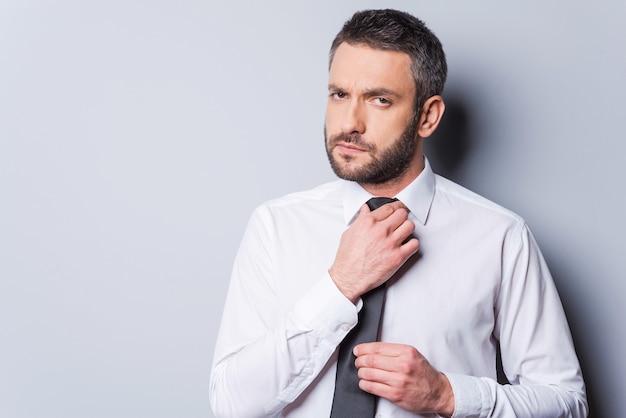 Готов к деловой встрече. уверенный зрелый мужчина поправляет галстук и смотрит в камеру, стоя на сером фоне