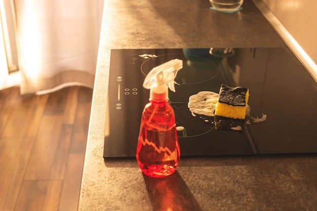 家庭の台所を掃除する準備ができて、テーブルトップと電気ストーブに洗剤ボトルと黄色いスポンジをスプレーします、モダンなキッチンのインテリア写真