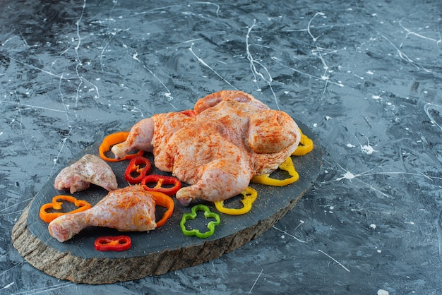 파란색 배경에 보드에 닭고기와 후추를 요리 할 준비가되었습니다. 무료 사진
