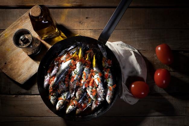 Готовая к приготовлению рыба с оливковым маслом, перцем и помидорами вокруг нее