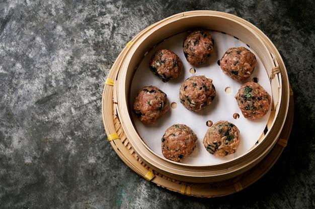 금속 책상 위에 아시아 대나무 증기선에서 미트볼을 요리 할 준비가되었습니다. 평면도. 플랫 레이.
