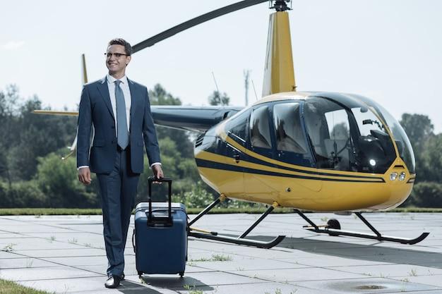 出発する準備ができました。ヘリポートに到着し、満足そうに笑いながらスーツケースを運ぶ明るい若いceo