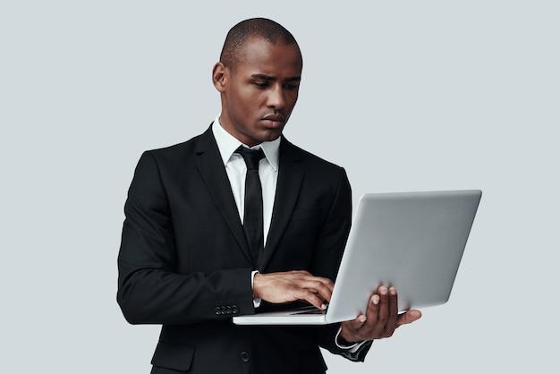 사업을 할 준비가 되었습니다. 회색 배경에 서 있는 동안 컴퓨터를 사용하여 작업하는 formalwear에서 젊은 아프리카 남자
