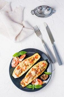 白いテーブルの上の黒いプレートにチーズとトマトとバジルの葉とカトラリーを詰めた、すぐに食べられる焼きズッキーニの半分。野菜メニュー、健康食品。上面図と垂直図