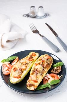 白いテーブルの上の黒いプレートにチーズとトマトとバジルの葉とカトラリーを詰めた、すぐに食べられる焼きズッキーニの半分。野菜メニュー、健康食品。垂直方向のビュー