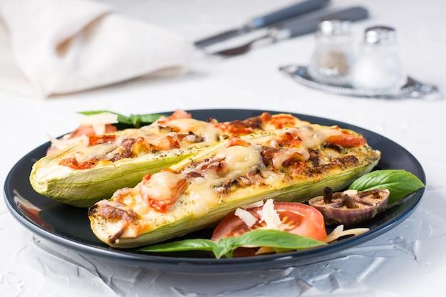 白いテーブルの上の黒いプレートにチーズとトマトとバジルの葉を詰めた、すぐに食べられる焼きズッキーニの半分。野菜メニュー、健康食品。閉じる