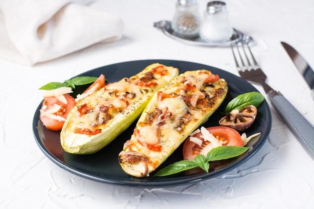 白いテーブルの上の黒いプレートにチーズとトマトとバジルの葉を詰めた、すぐに食べられる焼きズッキーニの半分。野菜メニュー、健康食品