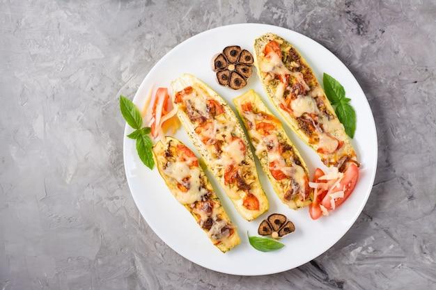 テーブルの上の皿にチーズとトマトとバジルの葉を詰めた、すぐに食べられる焼きズッキーニの半分。野菜料理、健康食品。上面図。コピースペース