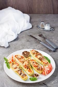 テーブルの上の皿にチーズとトマトとバジルの葉を詰めた、すぐに食べられる焼きズッキーニの半分。野菜料理、健康食品。垂直方向のビュー