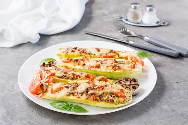 テーブルの上の皿にチーズとトマトとバジルの葉を詰めた、すぐに食べられる焼きズッキーニの半分。野菜料理、健康食品