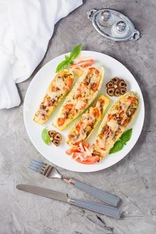 テーブルの上の皿にチーズとトマトとバジルの葉を詰めた、すぐに食べられる焼きズッキーニの半分。野菜メニュー、健康食品。垂直および上面図