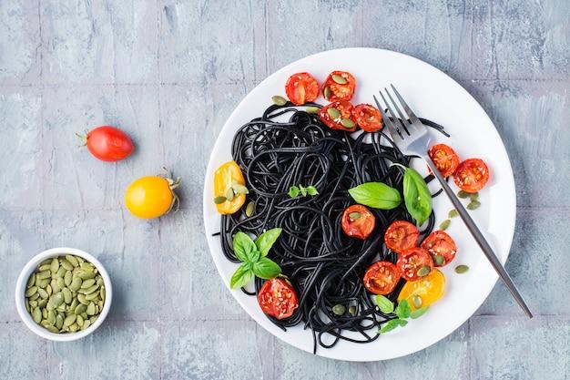 テーブルの上の皿にドライトマト、ゴマ、カボチャを添えた黒いスパゲッティを食べる準備ができました。グルメ食品。上面図。コピースペース