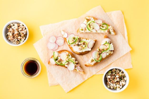 Готовая к употреблению брускетта с творогом, огурцом, редисом и проросшими зернами на бумаге на желтом столе. здоровые закуски. вид сверху
