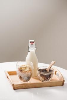 건강에 좋은 영양가 있는 아침 식사 준비 - 아몬드, 치아씨드, 바나나, 키위 과일, 딸기가 포함된 그래놀라, 우유가 든 항아리