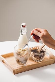 健康的な栄養価の高い朝食を食べる準備ができています-アーモンド、チアシード、バナナとキウイフルーツとベリーのグラノーラ、近くにミルクの入った瓶
