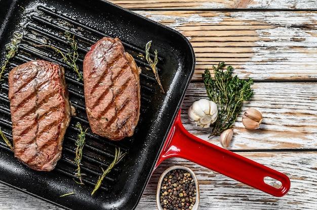 Готовый к употреблению стейк из говядины top blade, мясо блэк-ангус. серый фон. вид сверху. скопируйте пространство.