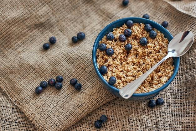 食べる準備ができました。ブルーベリー、孤立したボウルにオーツ麦と健康的で便利な朝食用シリアルの上面図。朝のヘルシーなおやつや朝食。ミューズリーの金属スプーン