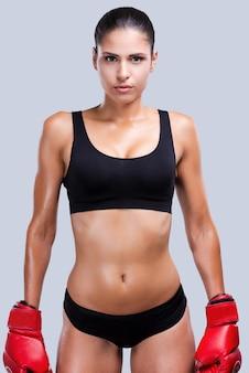 戦う準備ができました。灰色の背景に立っている間アートカメラを探しているボクシンググローブの魅力的な若いスポーティな女性