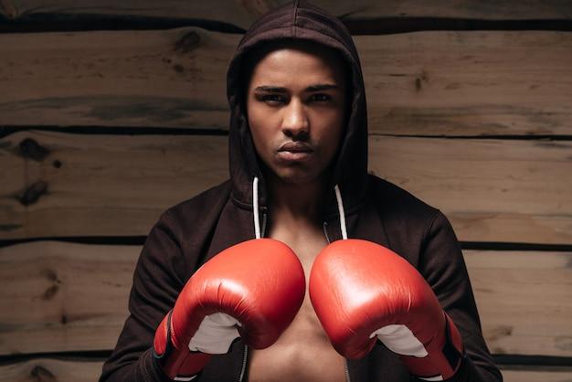 戦う準備ができました。フード付きシャツとボクシンググローブで自信を持って若いアフリカ人
