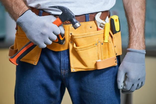 Готов починить все крупным планом ремонтника с поясом для инструментов с различными инструментами, держащими молоток