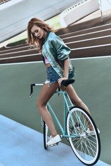 갈 준비가 되었습니다. 야외에서 자전거를 들고 캐주얼하게 서 있는 매력적인 젊은 여성의 전체 길이