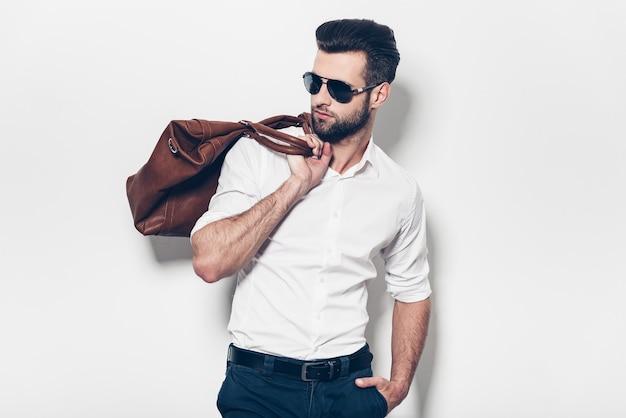 Готов идти. красивый молодой человек в белой рубашке несет кожаную сумку на плече и смотрит в сторону