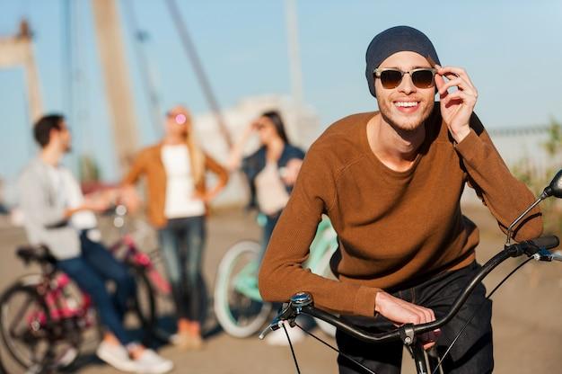 楽しむ準備ができました。彼の友人がバックグラウンドで話している間彼の自転車に寄りかかって彼のサングラスを調整しているハンサムな若い笑顔の男