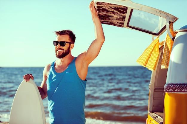 Готов повеселиться. улыбающийся молодой человек держит скимборд и открывает дверь багажника своего ретро-минивэна на фоне моря