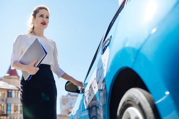 出発する準備ができました。彼女の書類を保持し、出発する準備ができている間に車を開く魅力的な素敵な自信のある実業家