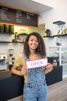 開く準備ができました。オープンと言うサインを示すバーの近くに立っているデニムのオーバーオールの若い大人の笑顔の女性