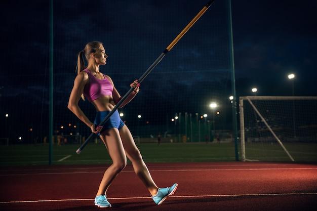 困難を克服する準備ができています。夕方、スタジアムでトレーニングするプロの女性棒高跳び選手。屋外で練習中。スポーツの概念