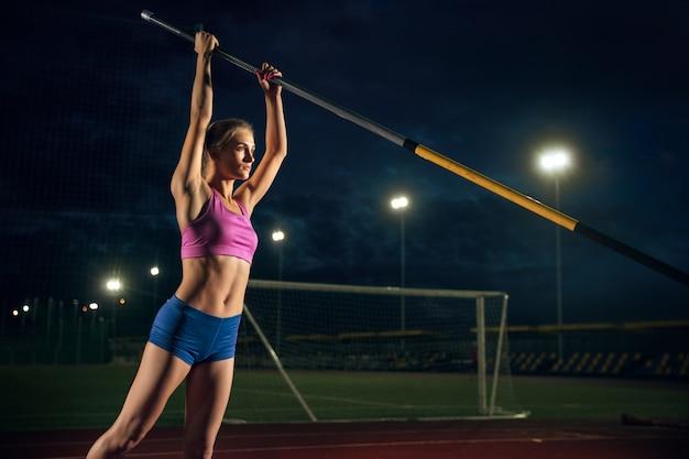 困難を克服する準備ができています。夕方、スタジアムでトレーニングするプロの女性棒高跳び選手。屋外で練習中。スポーツの概念 無料写真