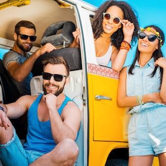 Готов к поездке. три веселых человека сидят в своем минивэне, а одна женщина, прислонившись к двери автомобиля, улыбается