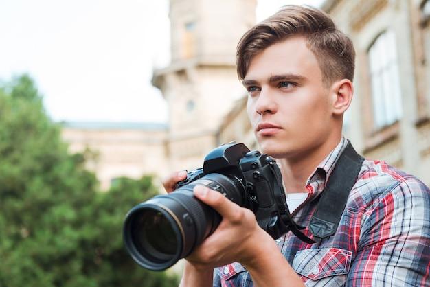 撮影する準備ができました。デジタルカメラを持って、屋外に立っている間目をそらしているハンサムな若い男