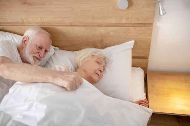 寝る準備ができました。妻を毛布で覆っている老人