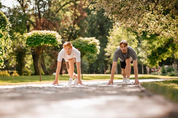 시작할 준비가 되었습니다. 화창한 아침에 공원 트랙에서 달리기 시작할 준비가 된 티셔츠와 반바지를 입은 두 명의 집중된 남자