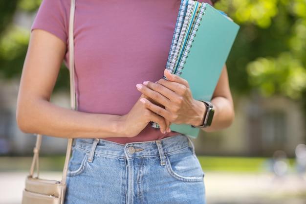 Готов учиться. девушка в розовой футболке держит в руках учебники