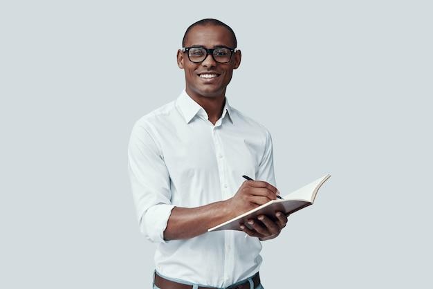 Готов учиться. красивый молодой африканский человек что-то записывает, стоя на сером фоне
