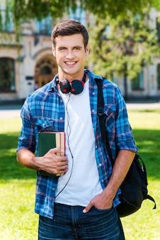 勉強する準備ができました。本を持って大学の前に立って笑っているハンサムな若い男