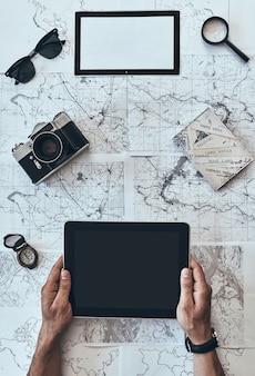 旅行する準備ができました。サングラスとデジタルタブレットを使用して男の上面図をクローズアップ