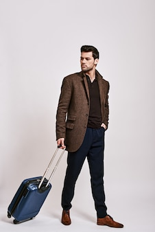 Готов к путешествию стильный темноволосый мужчина, стоящий с чемоданом и смотрящий в сторону, изолированный на сером
