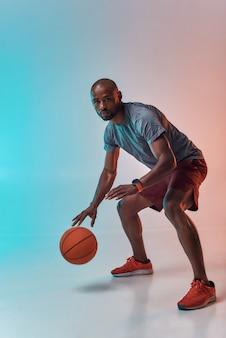 Готов к победе в полный рост уверенного в себе молодого африканца в спортивной одежде, играющего в баскетбол